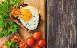 Rostat bröd med ägget och stekte tomater Royaltyfri Bild