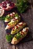 Rostat bröd med avokadot och granatäpplet på trätabellen arkivfoton