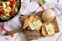Rostat bröd, med brieost och gräslökar och tagliatelle med Arkivfoton