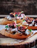 Rostat bröd med caramelized lökar, getost, jamon och grillade fikonträd Selektivt fokusera royaltyfri fotografi