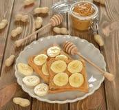 Rostat bröd med den jordnötsmör och bananen royaltyfria bilder