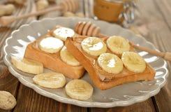 Rostat bröd med den jordnötsmör och bananen royaltyfri foto