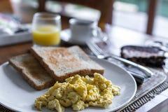 Rostat bröd med det stekte ägget, på den vita plattan i lyxig tropisk villa Läcker frukost med coffe och orange fruktsaft På a Royaltyfria Bilder