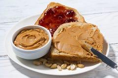 rostat bröd med jordnötsmör och driftstopp för frukost på den vita tabellen Arkivfoto