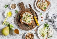 Rostat bröd med ost, päronet, honung och muttrar Läcker frukost eller mellanmål på en ljus bakgrund royaltyfria foton