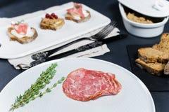 Rostat bröd med Parma, salami- och gåspate på en vit skärbräda fotografering för bildbyråer