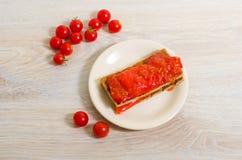 Rostat bröd med tomatketchup och röd peppar på en beige platta på ett l Royaltyfri Foto