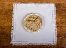 Rostat brödbröd i en vit platta på tappningträbakgrund arkivbilder