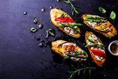 Rostat brödsmörgåsar med ost, peppar och sparriers på svart royaltyfri bild