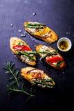 Rostat brödsmörgåsar med ost, peppar och sparriers på svart arkivbilder