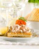 Rostat brödskagen - srimp och kaviar på rostat bröd Arkivbilder