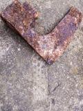 Rostat huvud av en bruten blixtrande yxa som ligger på en stenyttersida med en sniden pil på den Arkivfoton