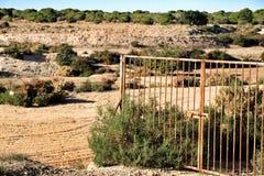 Rostat staket i busken och den övergav gropen i bakgrunden royaltyfria bilder