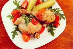 Rosted chicken with tomatoes, toned and cucumber. Rosted chicken with tomatoes and cucumber on wooden table, toned effect Royalty Free Stock Images