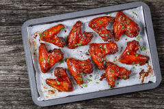 Rosted chicken wings on baking sheet. Delicious crispy roasted sticky Honey chicken Wings on baking sheet, on wooden table, easy recipe, view from above Stock Photography