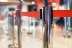 Rostfreie Barrikade mit rotem Seil auf einem unscharfen Innen-backgrou lizenzfreie stockfotos