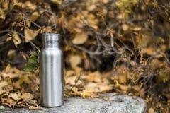 Rostfreie Isolierflasche auf den Steinschritten im Wald stockbild