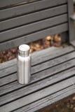 Rostfreie Isolierflasche auf Holzstuhl am Wald im Winter lizenzfreies stockbild