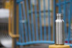 Rostfreie Isolierflasche mit einem Spielplatz der childrenÂs im Winterhintergrund stockbilder