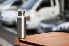 Rostfreie Isolierflasche mit Parkplatzhintergrund lizenzfreie stockfotografie