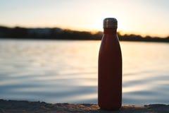 Rostfri röd thermo flaska för vatten Solnedgång och vatten på bakgrund arkivbilder