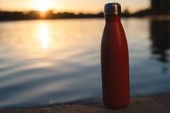 Rostfri röd thermo flaska för vatten Solnedgång och vatten på bakgrund royaltyfri bild