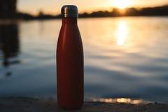 Rostfri röd thermo flaska för vatten Solnedgång och vatten på bakgrund arkivfoton