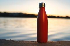 Rostfri röd thermo flaska för vatten Solnedgång och vatten på bakgrund arkivbild