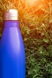 Rostfri termosvattenflaska, blåttfärg Modell på bakgrund för grönt gräs med solljuseffekt glansigt arkivbilder