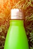 Rostfri termosvattenflaska, ljus - grön färg Modell som isoleras på bakgrund för grönt gräs med solljuseffekt Glansigt aluminium fotografering för bildbyråer