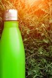 Rostfri termosvattenflaska, ljus - grön färg Modell som isoleras på bakgrund för grönt gräs med solljuseffekt Glansigt aluminium royaltyfria foton