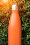 Rostfri termosvattenflaska, orange färg Modell som isoleras på bakgrund för grönt gräs med solljuseffekt Glansig aluminum vacu arkivbilder