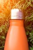 Rostfri termosvattenflaska, orange färg Modell som isoleras på bakgrund för grönt gräs med solljuseffekt Glansig aluminum vacu royaltyfria bilder