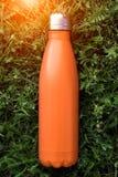 Rostfri termosvattenflaska, orange färg Modell som isoleras på bakgrund för grönt gräs med solljuseffekt Glansig aluminum vacu royaltyfri fotografi