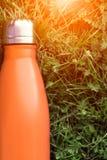 Rostfri termosvattenflaska, orange färg Modell som isoleras på bakgrund för grönt gräs med solljuseffekt Glansig aluminum vacu fotografering för bildbyråer