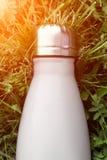 Rostfri termosvattenflaska, vit färg Modell som isoleras på bakgrund för grönt gräs med solljuseffekt Glansig aluminum vacuu royaltyfri foto
