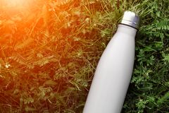 Rostfri termosvattenflaska, vit färg Modell som isoleras på bakgrund för grönt gräs med solljuseffekt Glansig aluminum vacuu fotografering för bildbyråer