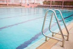 Rostfria ledstänger för stege för nedstigning in i simbassäng Simbassäng med ledstången Stege av en simbassäng royaltyfri bild