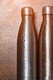 Rostfria thermo flaskor, på en trätabell som besprutas med vatten arkivfoto