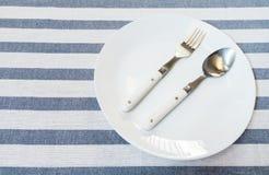Rostfritt stålsked och gaffel på den vita keramiska plattan som läggas på Wh Arkivfoto