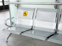 Rostfritt stålstolar i drevstationen med den rörelsehindrade signagen som gör bruket av drevservice för handikappade personer lät Royaltyfri Fotografi