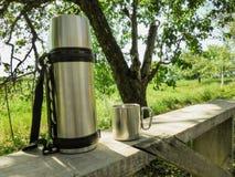 Rostfritt ståltermos- och koppställning på en bänk i trädgården i sommar fotografering för bildbyråer