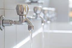 Rostfritt stålvattenkranar i badrummet av skolan Royaltyfri Bild