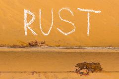 Rosthandschrift mit Kreide auf orange Metallhintergrund Lizenzfreies Stockfoto