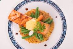 Rosti de color salmón asado a la parrilla con las verduras y bechamel y hollandaise Fotos de archivo