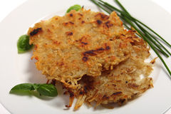Rosti potatoes. Traditional rosti potatoes in the Swiss style, garnished with chives and basil Stock Images