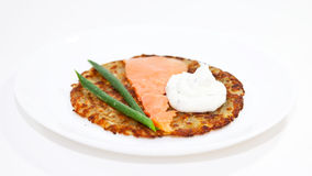 Rosti with salmon and sour cream. On the white plate Royalty Free Stock Images