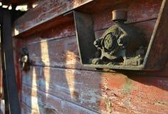 Rostig, åldrig och smutsig metallisk del på ett träbräde med skalad målarfärg - tappning - industriell nostalgi vid mekaniska app royaltyfria bilder