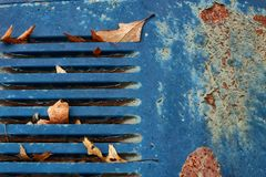 Rostig gammal övergiven bil för skrot med turkosskyddsgallret i bilkyrkogård royaltyfri bild