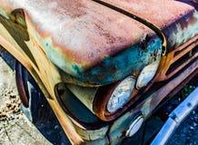 Rostig, gammal kastad bil i träna Arkivbilder